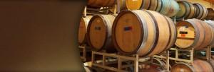 Wooden wine barrels on a rack in storage.