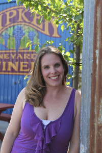 Ripken family member Sue at the winery leaning against the wall smiling.