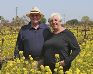 Ripken Wine family members, older couple standing in a mustard field with the yellow flowers in bloom.