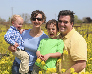 Ripken Wine family members, family of 4 with 2 children, all happy and standing in a mustard field with the yellow flowers in bloom.